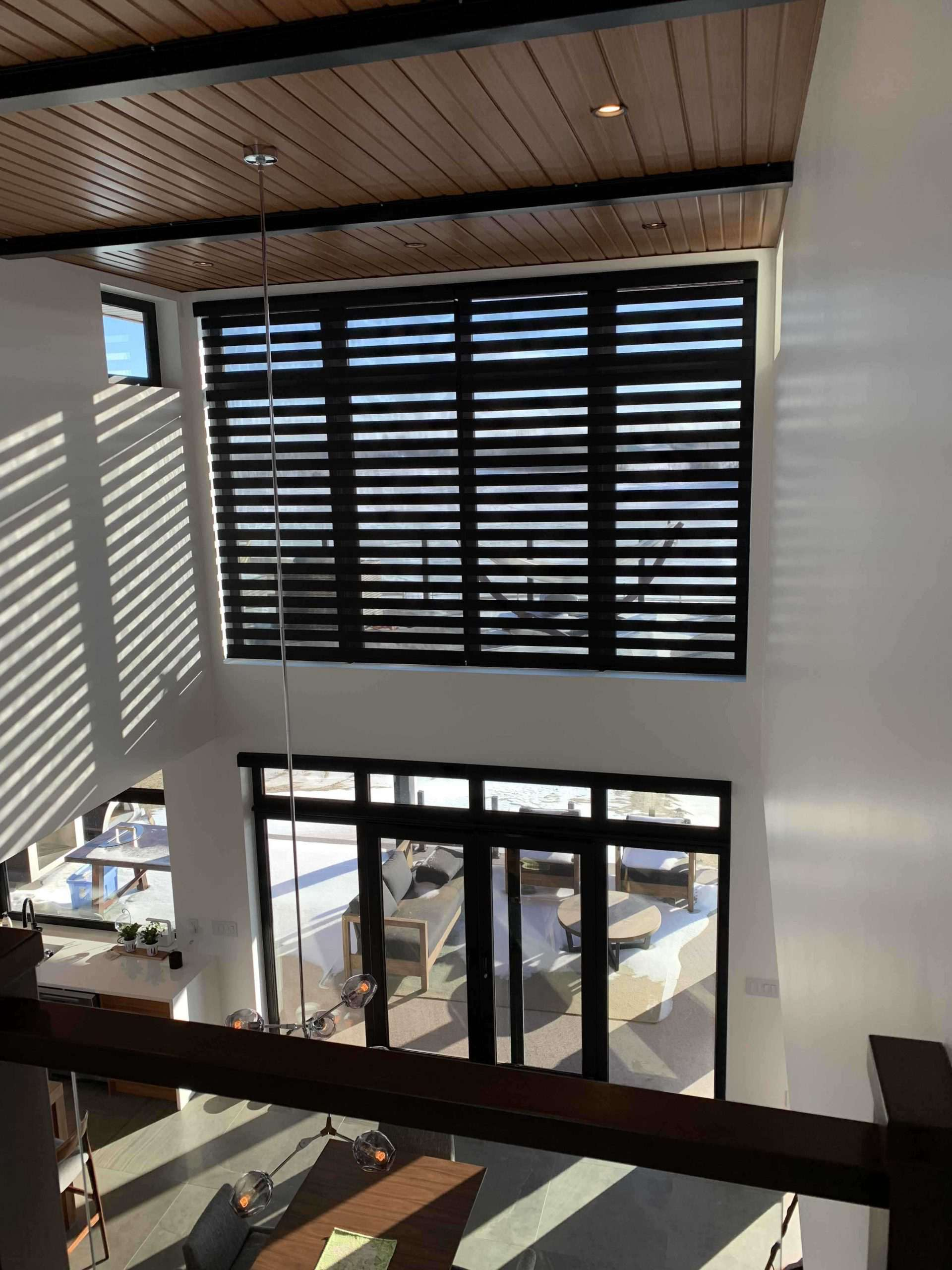 Indoor view of grand scale motorized blinds on second story window of a home over the patio doors to the back deck.